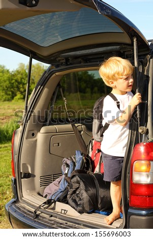 a young child is standing in the back of his minivan with a backpack on, looking outside and waiting for his family to come for a summer camping vacation - stock photo