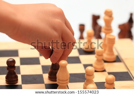A young child makes a move in a game of chess. - stock photo