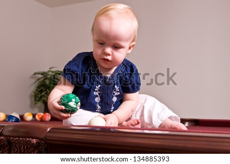 A young child sitting alone on a billiard table playing with the pool balls. She holds a green ball as she looks into the side pocket of the table. - stock photo