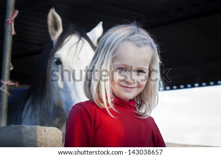 A young child standing in front of her horse, looking at the camera, positive feeling - stock photo