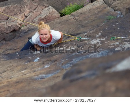 A young climber climbs on the vertical wall. - stock photo