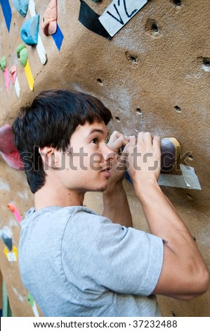 a young climber in a climbing gym - stock photo