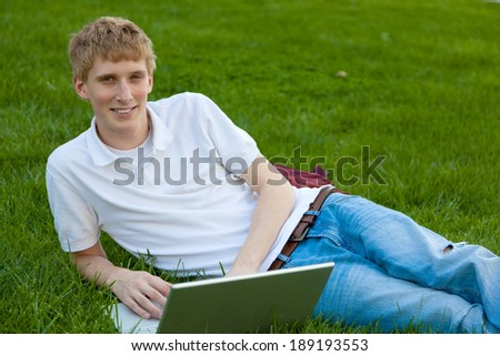 A young college age boy with a laptop computer sitting on grass outside - stock photo