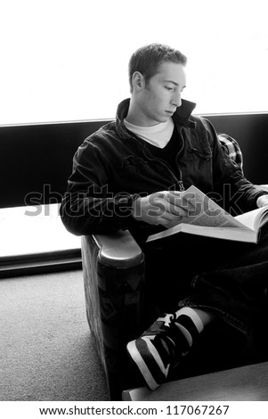 A young college aged man reading a book at the library in black and white. - stock photo