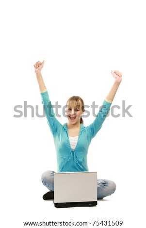 A young college girl sitting on the floor in front of her laptop, hands up - stock photo