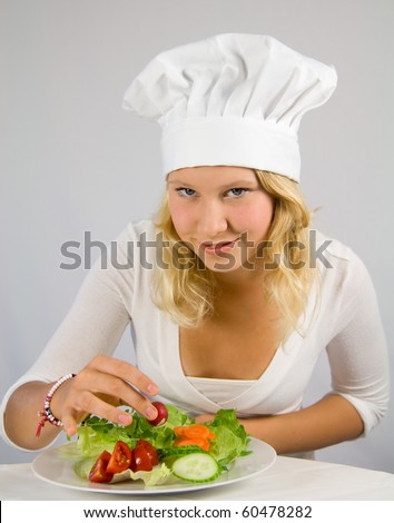 a young cook garnished salad - stock photo