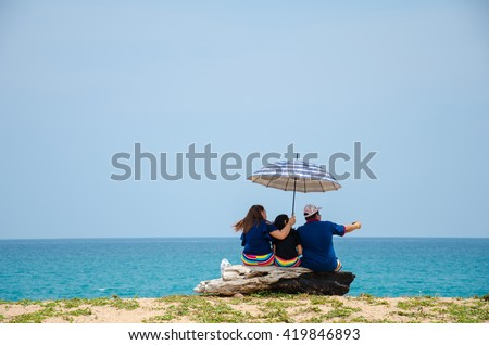 A young couple and their daughter are taking a selfie at the beach. - stock photo
