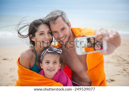 A young couple and their daughter are taking a selfie at the beach. Focus on the screen of the phone - stock photo