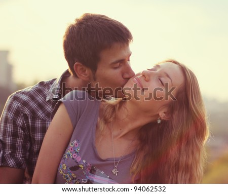 A young couple at sunset - stock photo