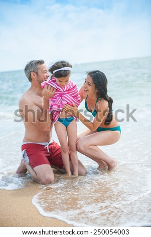 A young couple at the beach is posing in swimsuits with their daughter, Mom and dad are drying their six year old girl with a towel - stock photo