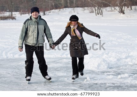 A young couple enjoys a leisurely skate in winter. - stock photo
