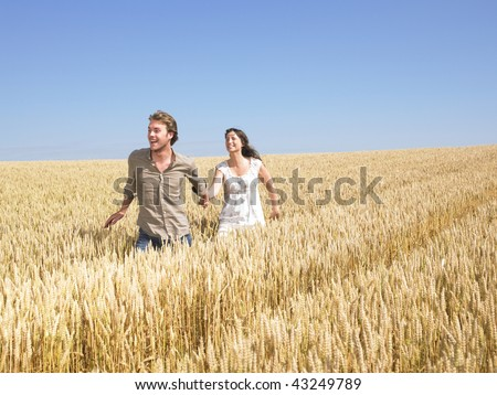 A young couple holding hands and walking through wheat field. Horizontally framed shot. - stock photo