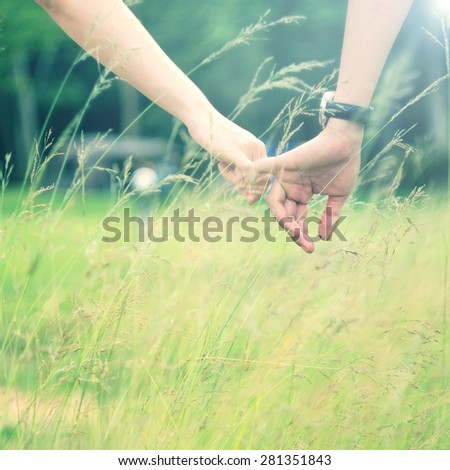 a young couple holding hands in grass field, outdoors - stock photo
