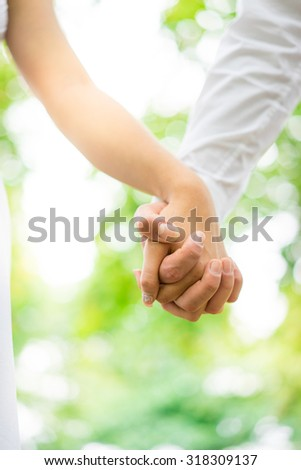 A young couple holding hands in the park, London. - stock photo
