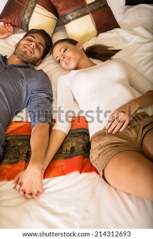A young couple holding hands while lying on the bed in a asian style hotel room. - stock photo
