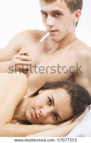 A young couple in bed with sad expressions. - stock photo