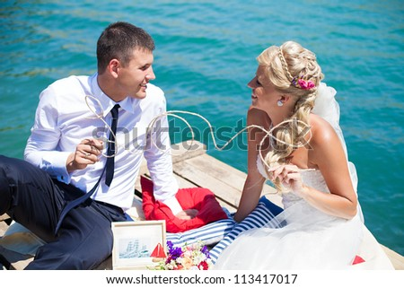 "A young couple in love bride and groom posing on the bridge background blue sea in their wedding day in summer.Together hold a decorated wire word ""LOVE"". Enjoy a moment of happiness and love. - stock photo"