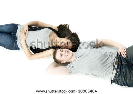 A young couple in love lying down together in a studio - stock photo