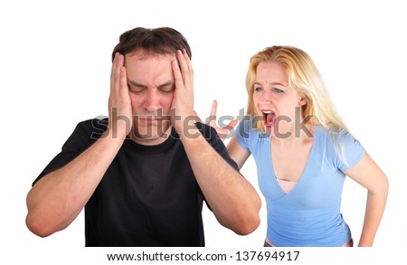 A young couple is fighting on a white isolated background. The girlfriend is yelling and screaming at the boyfriend who is stressed. - stock photo