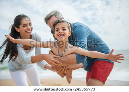 A young couple is holding their little girl like a plane - stock photo