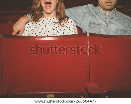 A young couple is watching a film in a movie theater, the woman is scared but her partner is looking relaxed - stock photo