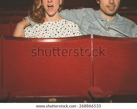 A young couple is watching an exciting  film in a movie theater - stock photo