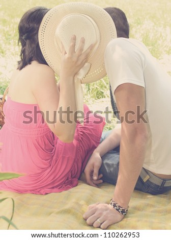 A young couple kissing having covered hat - stock photo