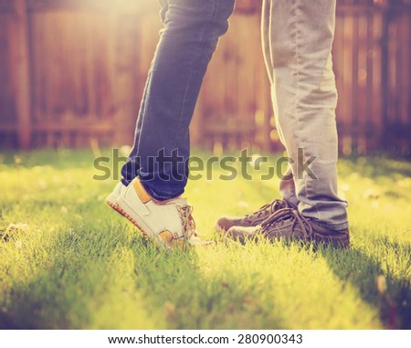 A young couple kissing in a backyard in summer sun light during sunset with dandelions blooming toned with a retro vintage instagram filter (VERY SHALLOW DOF on legs) - stock photo