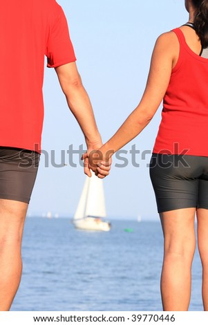 A young couple looks at the sailboat - stock photo