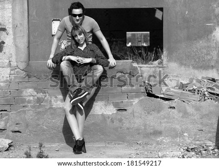 A young couple outside an industrial building ruin - stock photo