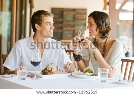 A young couple sitting at a table at an outdoor restaurant - stock photo