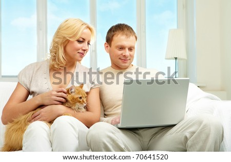 A young couple sitting on sofa and looking at laptop screen - stock photo