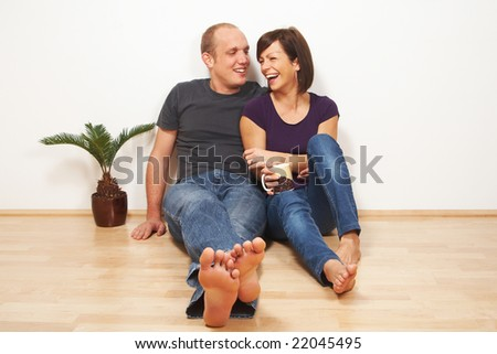 A young couple sitting on the floor in their living room. The young woman is laughing. - stock photo