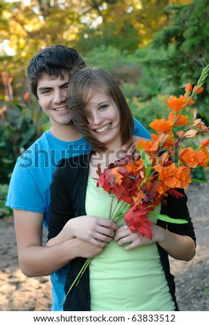 A young couple smiling during the fall - stock photo