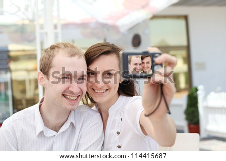 A young  couple  taking their photo on a digital camera in cafe - stock photo