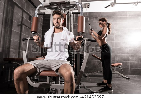 A young couple training together in the Gym. - stock photo
