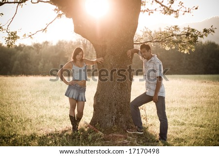 A young couple under the old tree in the nature - stock photo