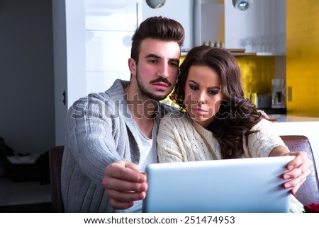 A young couple using in the evening their laptop computers at home and visiting a strange website.  - stock photo