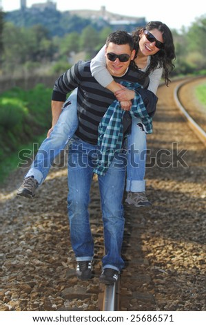 A young couple walking on a railway track - stock photo