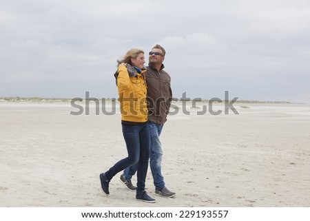 A young couple walks on the sandy beach in autumn - stock photo