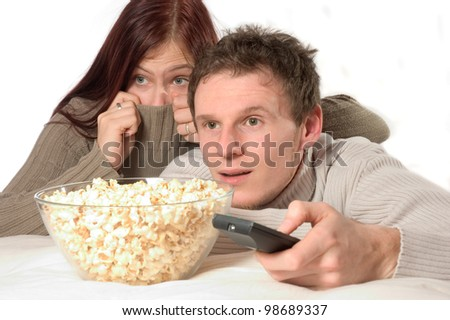 a young couple watches a horror movie - stock photo