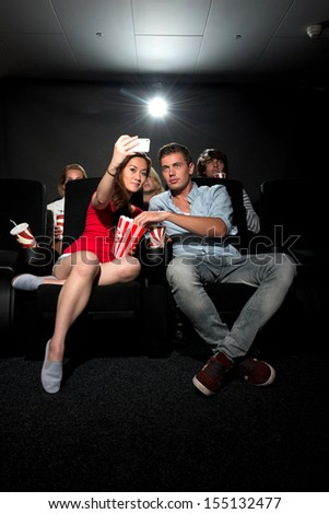 A young couple watching a movie at a cinema and photographing themselves with a Smartphone - stock photo