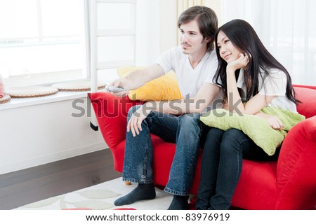 a young couple watching TV - stock photo