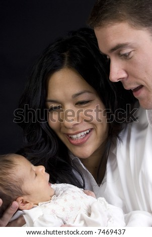 A young couple with a newborn girl. Family, love, caring. - stock photo