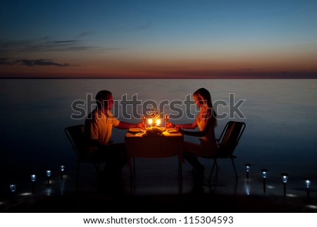 A young couple with a romantic dinner with candles on the sea sand beach - stock photo