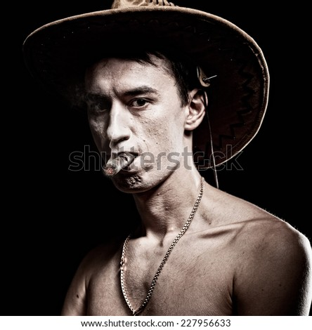 A young cowboy smoking on a black back ground. - stock photo