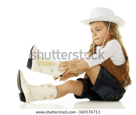 A young cowgirl concentrating as she puts on her boots.  On a white background. - stock photo