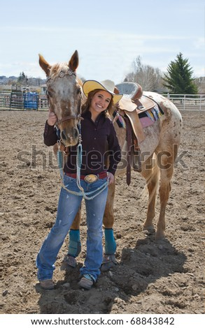 A young cowgirl poses with her horse. - stock photo
