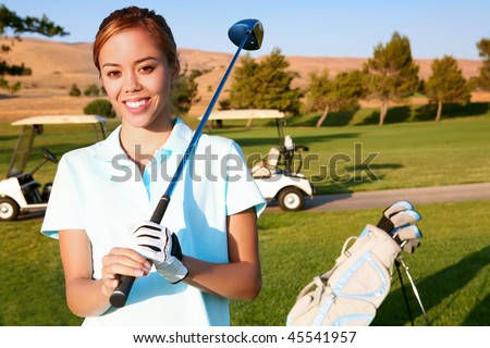 A young, cute woman golfer ready to hit on the fairway - stock photo