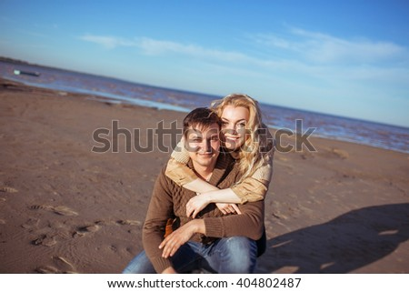 A young dark-haired man is sitting on his haunches on the sand and a young fair-haired woman is standing behind him and embracing him. Clothes: casual. - stock photo
